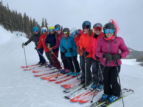 Nine woman line up at Crested Butte, all skiing on Elan Ripstick skis.