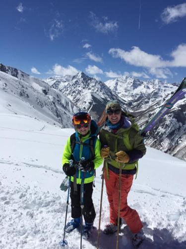 Krista Crabtree and her daughter pose for a picture after hiking with skis on their backs, with incredible Aspen-area mountain in the background.