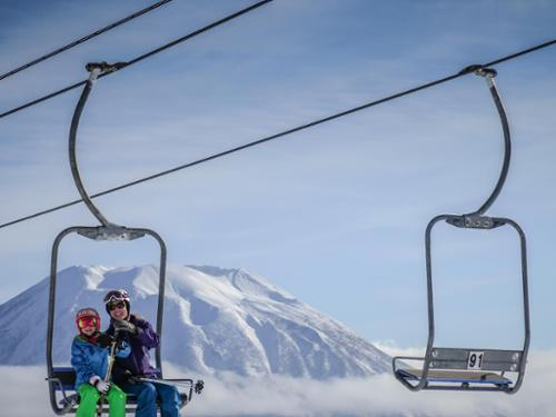 Krista Crabtree and her daughter ride a chairlift with Japan's Mt. Yotei volcano in the background.