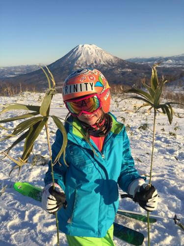 Krista Crabtree's daughter holds up bamboo leaves with Japan's Mt. Yotei in the background.