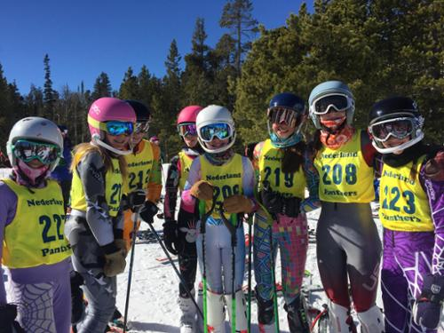 Middle school ski racers pose in their race bibs before their race.