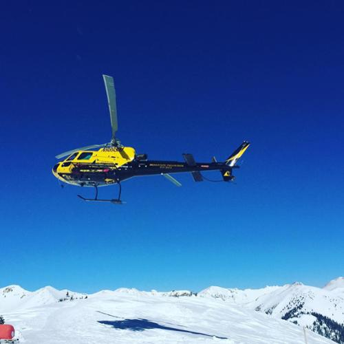 The Silverton Mountain helicopter flies with blue ski background.