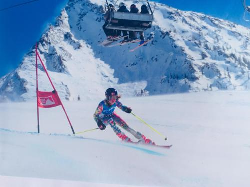 A girl racer skis fast in a super G with Crested Butte's peak behind her.