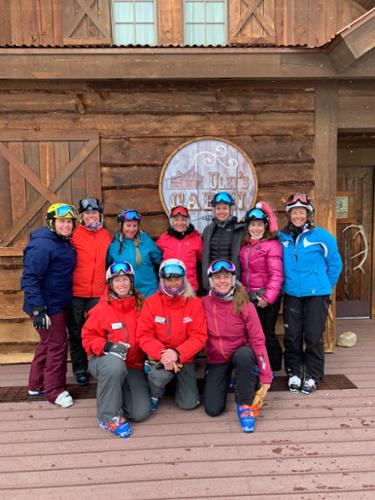 A group of female skiers pose in front of a restaurant at Crested Butte.