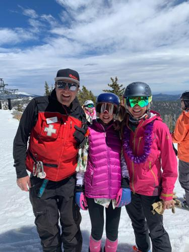 A ski patroller, a junior racer and mom pose at the top of Eldora Mountain Resort.