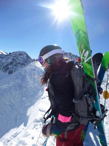 A skier with skis on her back completes her hike at Silverton and contemplates her line.