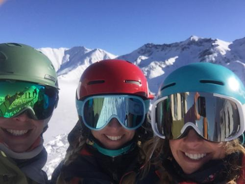 Three women in helmets, goggles and big smiles celebrate the day at Silverton Mountain.