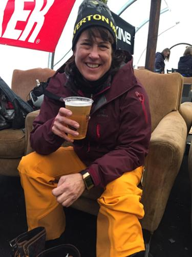 A woman drinks a beer in the yurt after skiing at Silverton Mountain.
