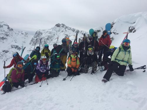 A group of women pose for a picture at the top of a cornice at Silverton Mountain.